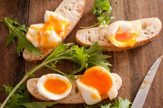 Soft boiled eggs broken open on baguettes
