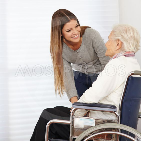 Woman talking to senior citizen in wheelchair