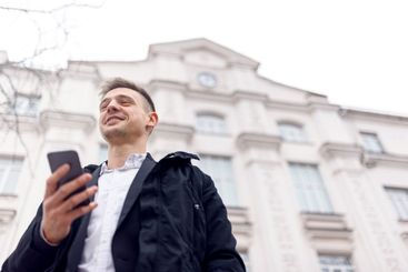 Smiling young male standing with smartphone outdoors