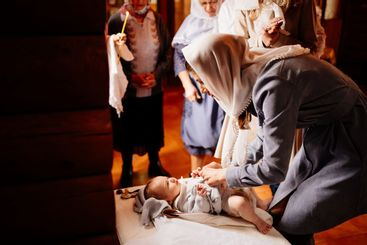 mom dress their child in the Church on a table. the...