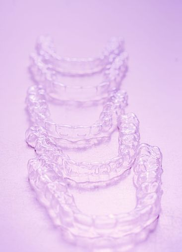 Invisible dental teeth brackets tooth aligners on pink...