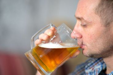 The man is drinking a fresh, cold beer from a large mug