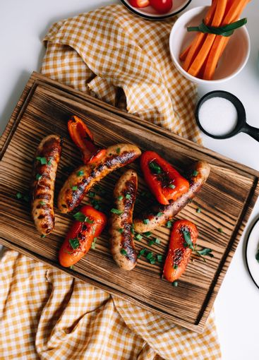 Grilled sausages and bell peppers on a wooden board.