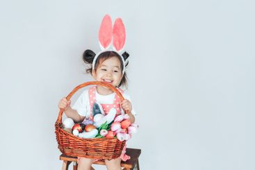 A little girl dressed as a rabbit holding a large basket...