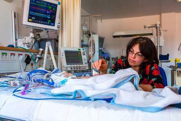 Mamma som vakar vid sitt barn på intensivvårdsavdelning .