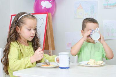 Little girl and boy is eating in kindergarten.