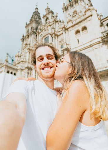 Young couple kissing in front of a cathedral during a...