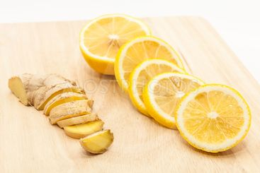 Ginger and lemon slices on wooden cutting board
