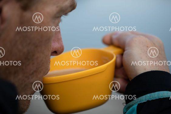 man dricker kaffe ur kåsa