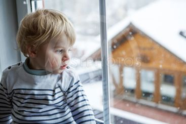 Little toddler boy looking out of the window on winter...