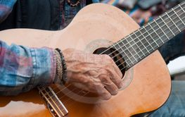 hands of old man playing on acoustic guitar...