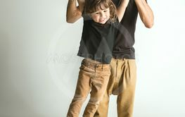 Father playing with young son against white studio...