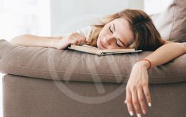 Tired relaxed woman sleep with book on sofa