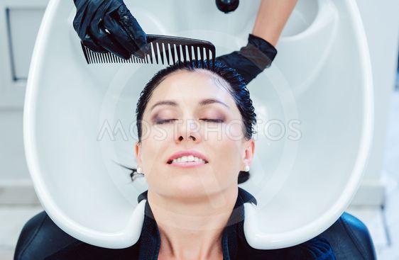 Artisan hairdresser washing hair of customer woman