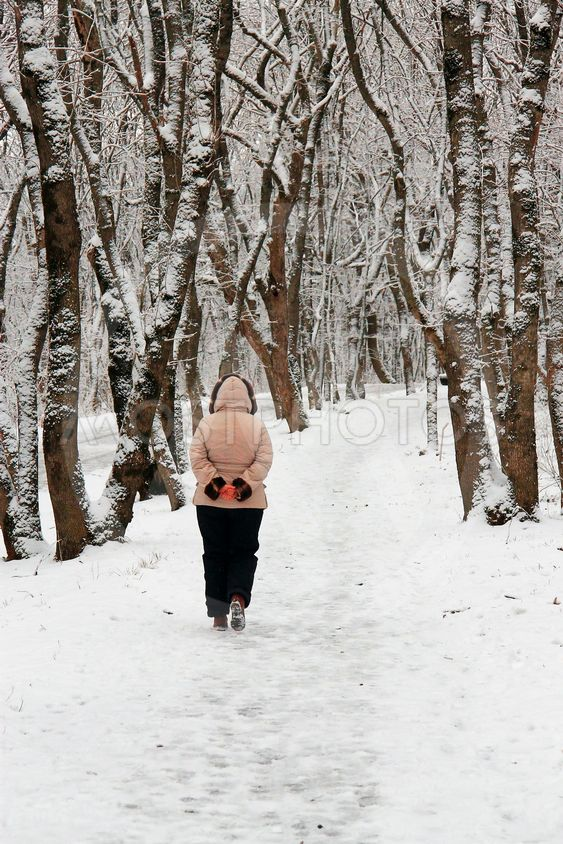 Woman walking alone in the winter park outdoor