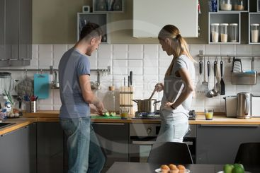 Young man and woman, couple cooking together in kitchen