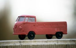Profile view of orange Volkswagen van toy miniature in...