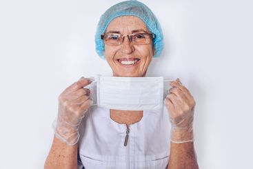 Elderly happy mature woman doctor or nurse in a white...