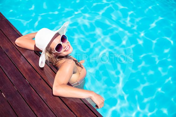 Beautiful woman wearing sunglasses and straw hat leaning...