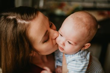 A mother holds a baby in her arms. A mom kisses a...