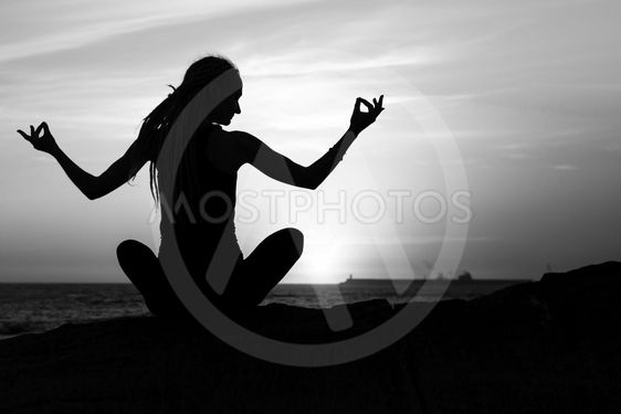 Black-and-white silhouette of yoga woman meditation on...