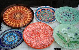 Ceramic plates, hand-painted with a dot pattern, are on...