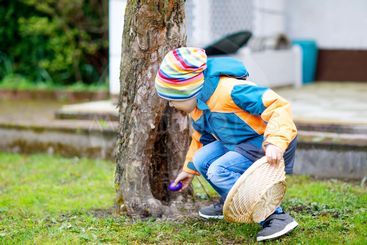 Cute adorable little kid boy making an egg hunt on Easter.