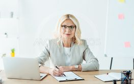 cheerful woman holding pen near clipboard and laptop in...