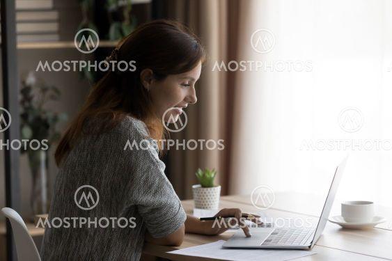 Smiling woman using laptop, working online, sitting at...