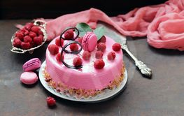 amazing pink cake with raspberries on an iron table