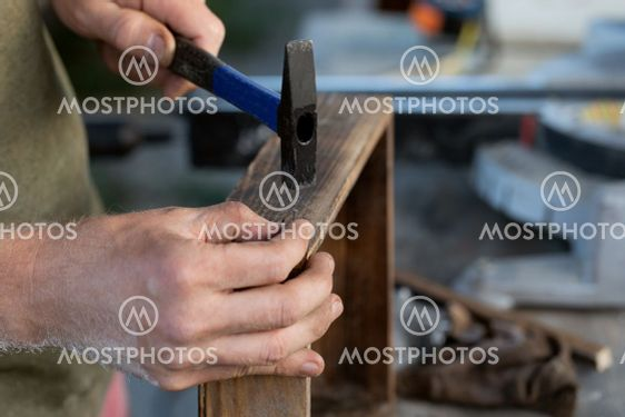 carpenters are preparing to hammer nail into wooden product