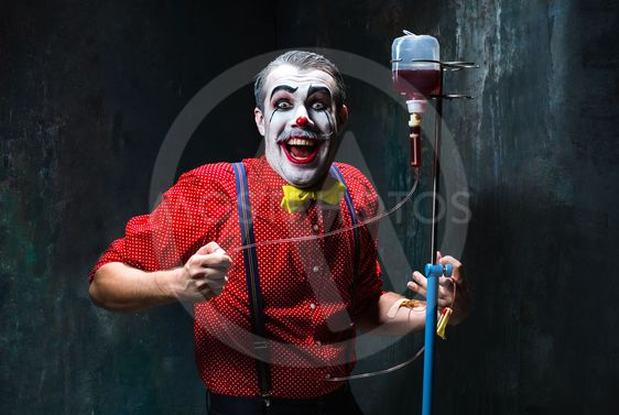 The scary clown and drip with blood on dack background....