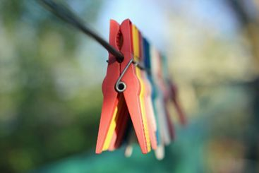 Colorful clothespins hanging in a row on clothesline in...