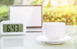 Coffee cup and laptop at office with digital clock