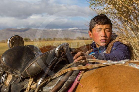 Kazakh Berkutchi (Eagle hunter) do saddles horse. In...