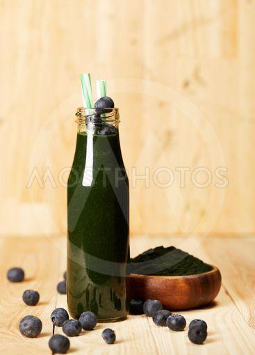 bowl with spiruluna powder, bottle of spirulina smoothie...