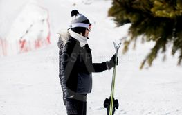 Young woman with ski equipment spending winter vacation...