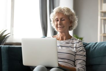 Smiling older woman looking at laptop screen, sitting on...