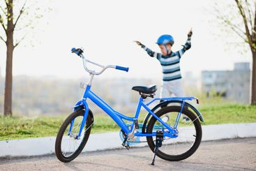 Cute child in helmet and protection stands near his bike