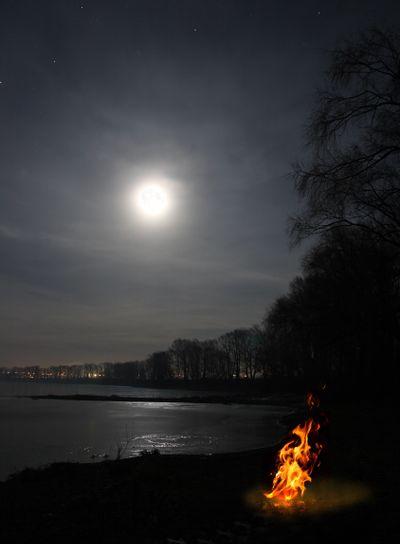 bonfire flame and moon over lake