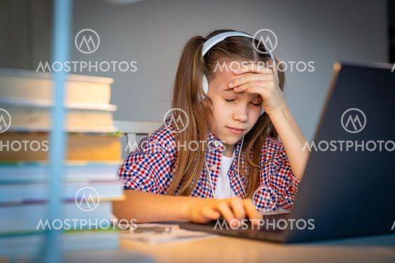 tired teen schoolgirl in headphones listen music