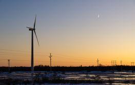 Solnedgång med vindkraftverk och elledningar
