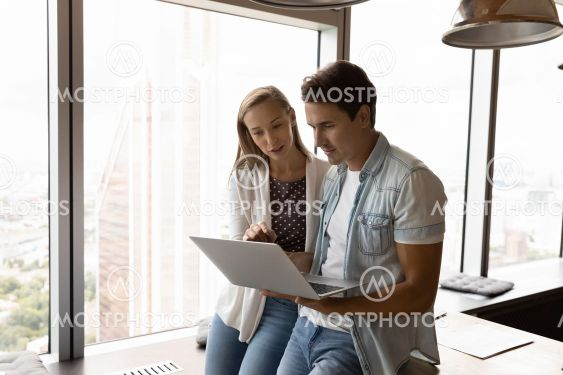 Successful young employees cooperate on laptop in office