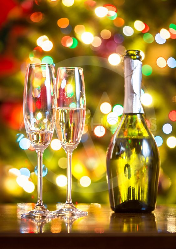 champagne flutes and bottle on table against Christmas...