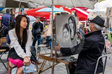 Street artist is painting a woman in Montmartre, Paris