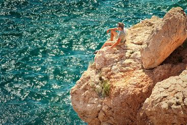 Young Man relaxing on rocky cliff with blue Sea on...