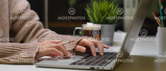 Female typing on laptop on office desk with a cup of...