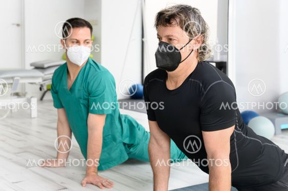 Therapist with protective face mask Assisting patient...