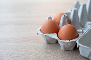 A carton of three fresh red free range eggs