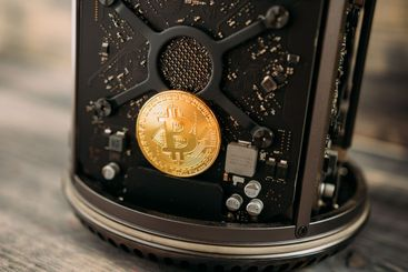 Bitcoin gold coin lies on the motherboard of the computer